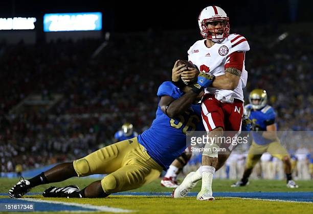 Quarterback Taylor Martinez of the Nebraska Cornhuskers is tackled for a safety by defensive end Datone Jones of the UCLA Bruins in the fourth...