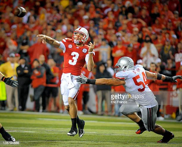 Quarterback Taylor Martinez of the Nebraska Cornhuskers launches the ball down field over defensive tackle John Simon and the Ohio State Buckeyes...