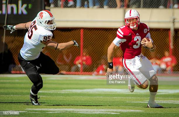 Quarterback Taylor Martinez of the Nebraska Cornhuskers runs past defensive lineman Jake Rouser of the Idaho State Bengals during their game at...