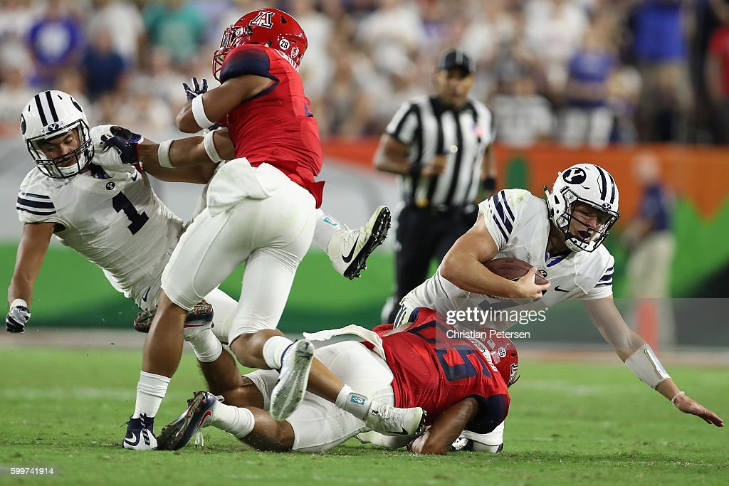 Quarterback Taysom Hill #7 of the Brigham Young Cougars is tackled by safety Anthony Mariscal #25 of the Arizona Wildcats during the college football game at University of Phoenix Stadium on September 3, 2016 in Glendale, Arizona. The Cougars defeated the Wildcats 18-16.