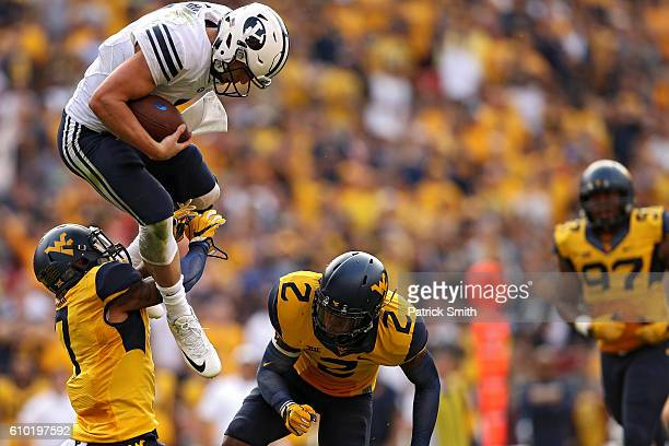 Quarterback Taysom Hill of the Brigham Young Cougars jumps between Khairi Sharif and Jeremy Tyler of the West Virginia Mountaineers during the second...