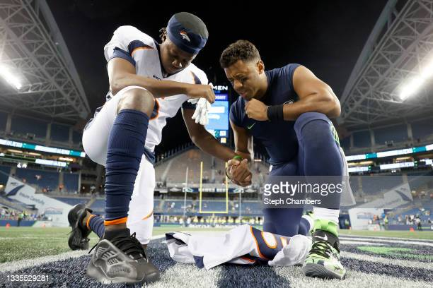 Quarterback Teddy Bridgewater of the Denver Broncos and quarterback Russell Wilson of the Seattle Seahawks pray after an NFL preseason game at Lumen...