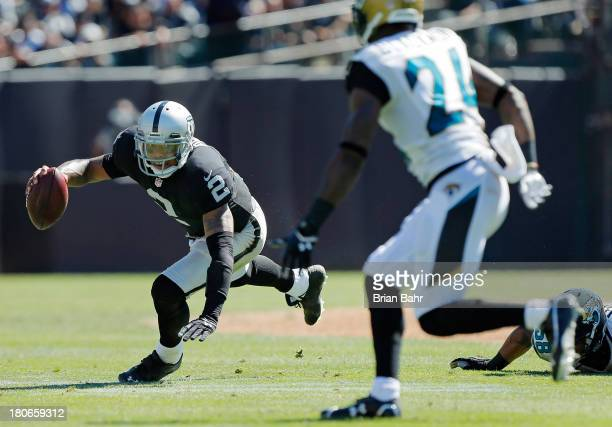 Quarterback Terrelle Pryor of the Oakland Raiders trips up as he breaks out of the pocket against the Jacksonville Jaguars on September 15 2013 at...