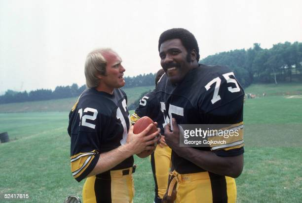 Quarterback Terry Bradshaw and defensive tackle Mean Joe Greene of the Pittsburgh Steelers share a laugh on the practice field during training camp...
