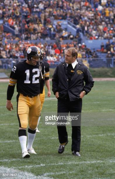 Quarterback Terry Bradshaw and head coach Chuck Noll of the Pittsburgh Steelers walk off the field after the first half of an NFL game against the...