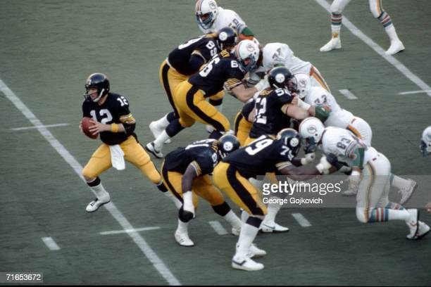 Quarterback Terry Bradshaw of the Pittsburgh Steelers drops back behind the blocking of offensive linemen Bennie Cunningham, Ted Petersen, Mike...