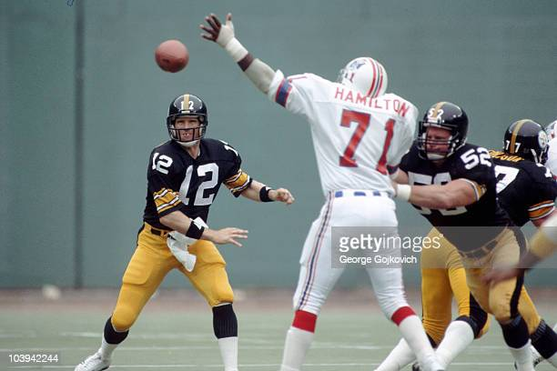 Quarterback Terry Bradshaw of the Pittsburgh Steelers passes as center Mike Webster blocks defensive lineman Ray Hamilton of the New England Patriots...