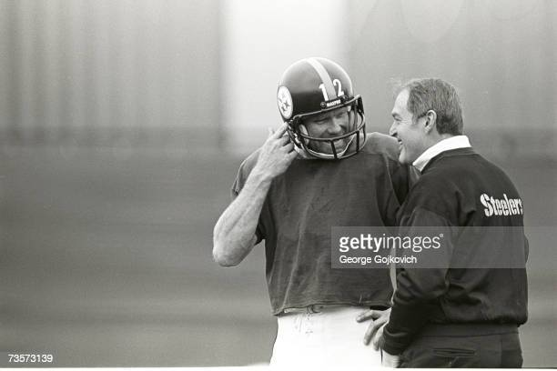Quarterback Terry Bradshaw of the Pittsburgh Steelers talks with head coach Chuck Noll during a practice session at a field next to Three Rivers...