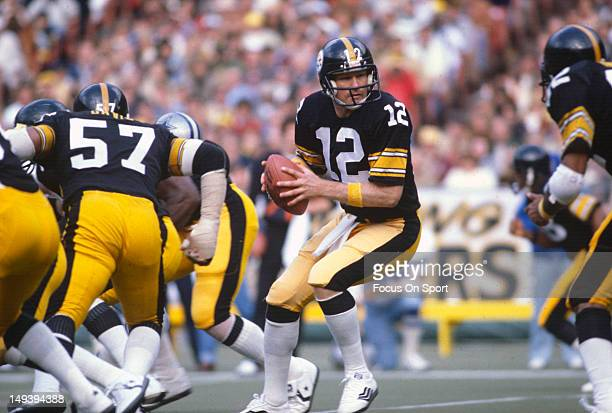 Quarterback Terry Bradshaw of the Pittsburgh Steelers turns to hand the ball off to a running back against the Dallas Cowboys during an NFL football...