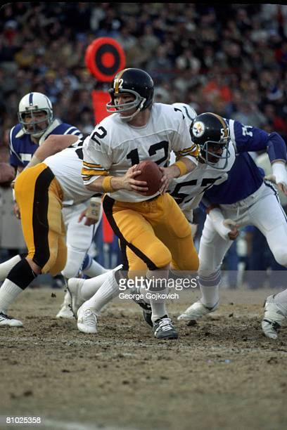 Quarterback Terry Bradshaw of the Pittsburgh Steelers turns to hand off the football during a playoff game against the Baltimore Colts at Memorial...