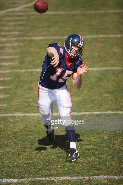 quarterback throwing a pass - quarterback stock-fotos und bilder