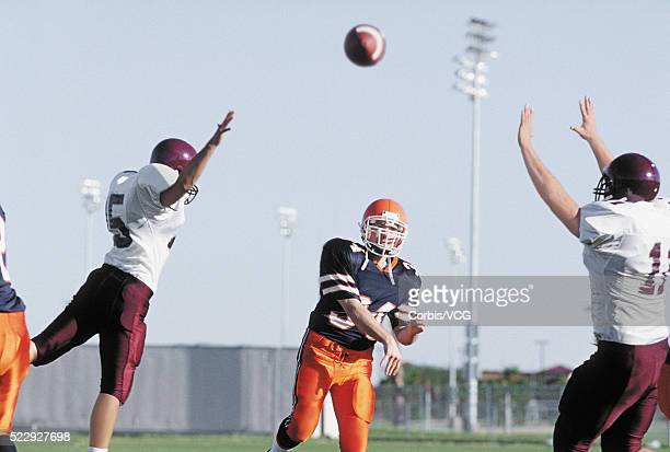 quarterback throwing football pass defenders - quarterback stock photos and pictures