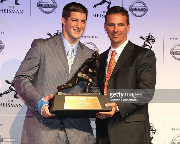 Quarterback Tim Tebow and head coach Urban Meyer of the Florida Gators hold up the Heisman Trophy at the Hard Rock Cafe on December 8 2007 in New...