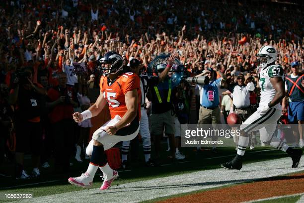Quarterback Tim Tebow of the Denver Broncos celebrates his touchdown run in the first half against the New York Jets at INVESCO Field at Mile High on...