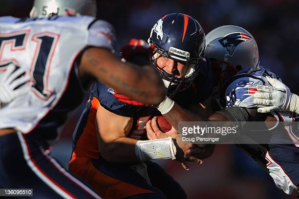 Quarterback Tim Tebow of the Denver Broncos is tackled by strong safety James Ihedigbo of the New England Patriots at Sports Authority Field at Mile...
