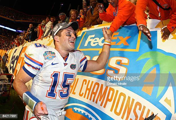Quarterback Tim Tebow of the Florida Gators celebrates with fans after defeating the Oklahoma Sooners in the FedEx BCS National Championship Game at...