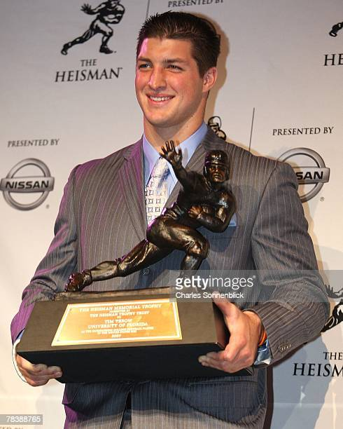 Quarterback Tim Tebow of the Florida Gators holds up the Heisman Trophy after being the first sophmore to win the award at the Hard Rock Cafe on...