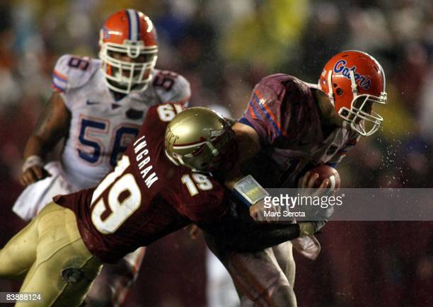 Quarterback Tim Tebow of the Florida Gators is brought down by linebacker Kenny Ingram of the Florida State Seminoles at Bobby Bowden Field at Doak...
