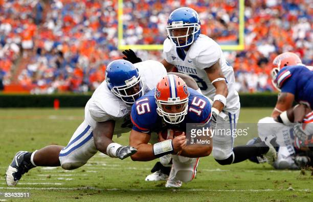 Quarterback Tim Tebow of the Florida Gators is tackled by linebacker Sam Maxwell of the Kentucky Wildcats during the game at Ben Hill Griffin Stadium...