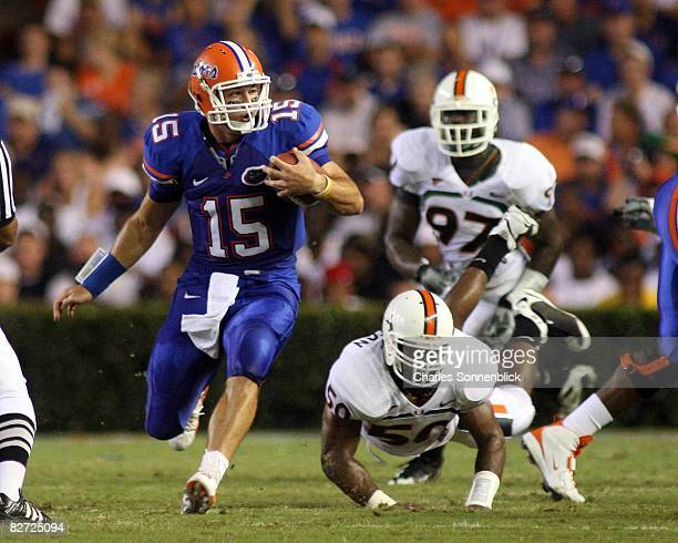 Quarterback Tim Tebow of the Florida Gators picks up a first down while avoiding linebacker Darryl Sharpton of the Miami Hurricanes on August 30 2008...