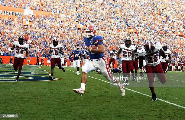 Quarterback Tim Tebow of the Florida Gators runs for a touchdown that was called back on a penalty in the first quarter against the Troy Trojans at...