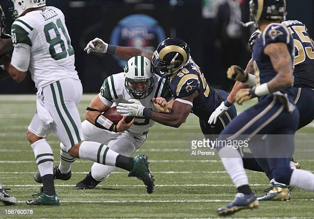 Quarterback Tim Tebow of the New York Jets fights off Linebacker Josh Hull as he runs the Wildcat against the St Louis Rams at Edward Jones Dome on...