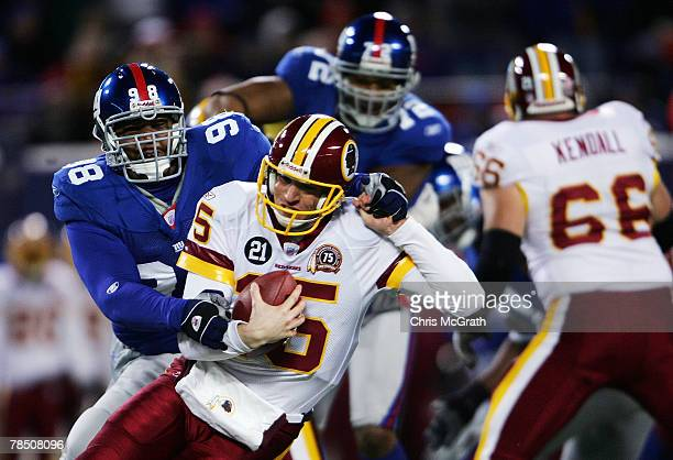 Quarterback Todd Collins of the Washington Redskins is sacked by Fred Robbins of the New York Giants at Giants Stadium on December 16 2007 in East...
