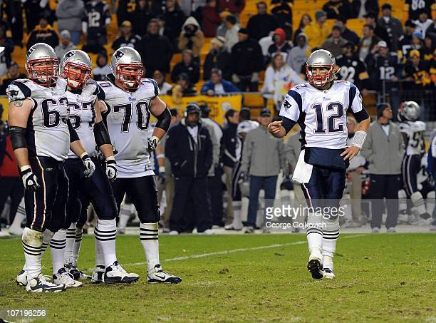 Quarterback Tom Brady and offensive linemen Dan Connolly, Dan Koppen and Logan Mankins of the New England Patriots look to the sideline during a game...