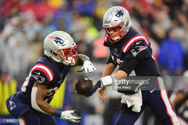 Quarterback Tom Brady hands off to running back James White of the New England Patriots in the second quarter of the game against the Cleveland...