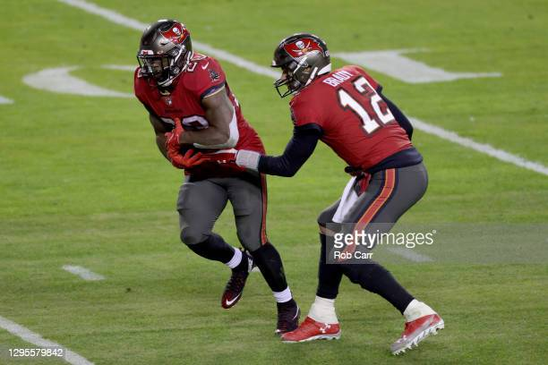 Quarterback Tom Brady hands the ball off to running back Leonard Fournette of the Tampa Bay Buccaneers during the first half of the NFC Wild Card...