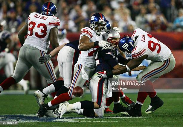 Quarterback Tom Brady of the New England Patriots fumbles the football after being hit hard by Osi Umenyiora and Justin Tuck of the New York Giants...