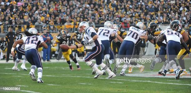 Quarterback Tom Brady of the New England Patriots hands off to running back BenJarvus Green-Ellis behind the blocking of offensive linemen Matt...