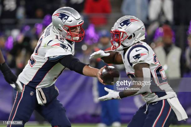 Quarterback Tom Brady of the New England Patriots hands the ball off to running back James White during the first half against the Baltimore Ravens...