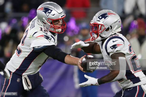 Quarterback Tom Brady of the New England Patriots hands-off to running back James White of the New England Patriots against the Baltimore Ravens...