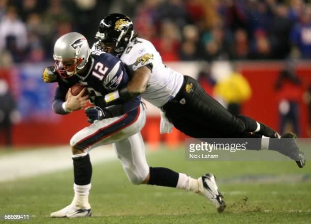 Quarterback Tom Brady of the New England Patriots is sacked by Mike Peterson of the Jacksonville Jaguars in the first quarter of their AFC Wildcard...