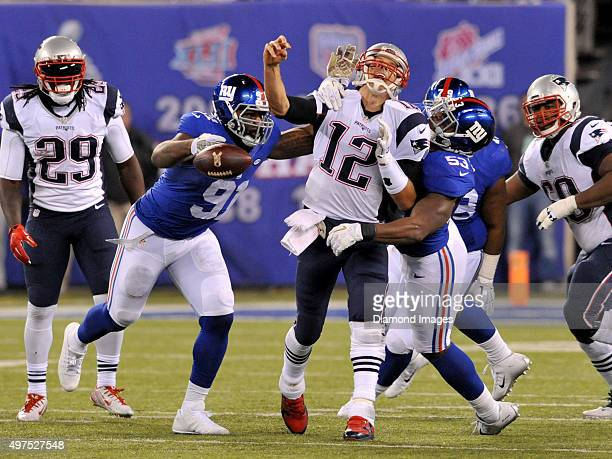 Quarterback Tom Brady of the New England Patriots is stripsacked by linebacker Jasper Brinkley of the New York Giants during a game on November 15...
