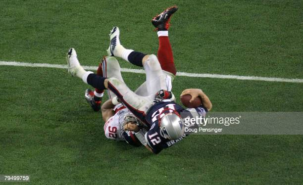 Quarterback Tom Brady of the New England Patriots lies on his back after being sacked by defensive end Michael Strahan of the New York Giants in the...