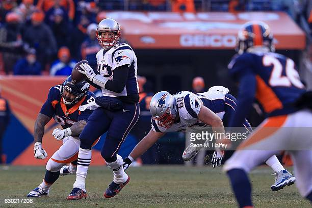 Quarterback Tom Brady of the New England Patriots looks down the field for a receiver under pressure by defensive end Billy Winn of the Denver...