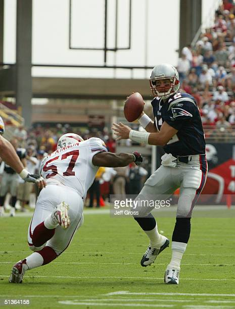 Quarterback Tom Brady of the New England Patriots looks to pass as he is rushed by Ronald McKinnon of the Arizona Cardinals andat Sun Devil Stadium...