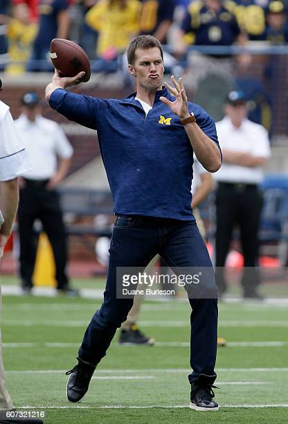 Quarterback Tom Brady of the New England Patriots plays catch with head coach Jim Harbaugh of the Michigan Wolverines before a game against the...