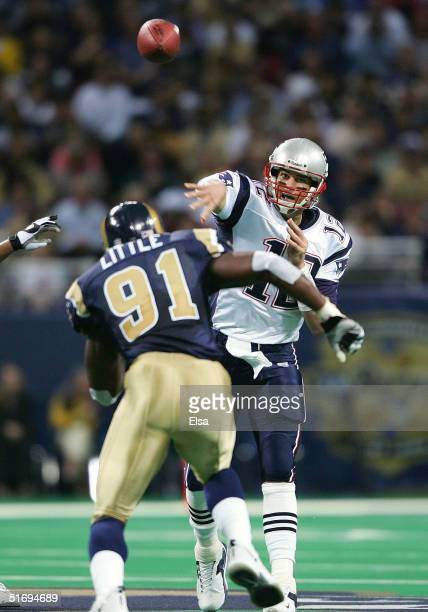 Quarterback Tom Brady of the New England Patriots pressured by Leonard Little of the St Louis Rams completes a pass to Kevin Faulk in the first half...