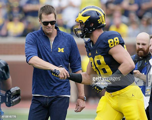 Quarterback Tom Brady of the New England Patriots shakes hands with Jake Butt of the Michigan Wolverines after being an honorary captain for a game...