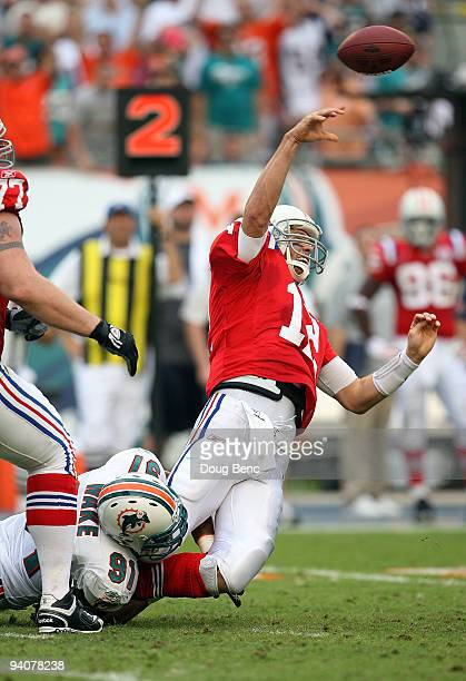 Quarterback Tom Brady of the New England Patriots throws an interception late in the game while being hit by linebacker Cameron Wake of the Miami...