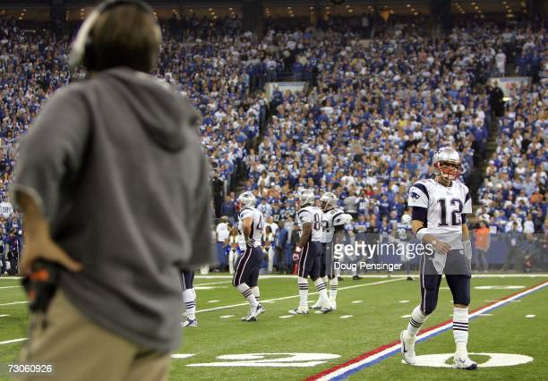 Quarterback Tom Brady of the New England Patriots walks off the field as head coach Bill Belichick looks on during the AFC Championship Game against...