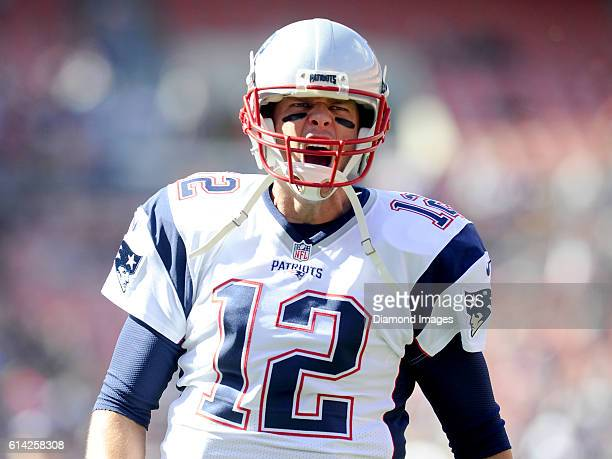 Quarterback Tom Brady of the New England Patriots yells toward the crowd as he runs onto the field prior to a game against the Cleveland Browns on...