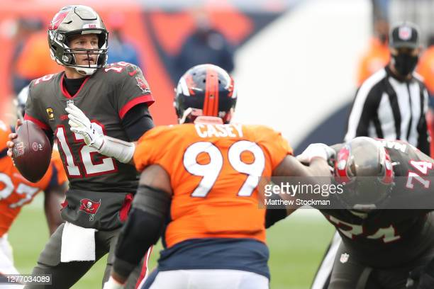 Quarterback Tom Brady of the Tampa Bay Buccaneers looks to pass as he is pressured by defensive end Jurrell Casey of the Denver Broncos during the...