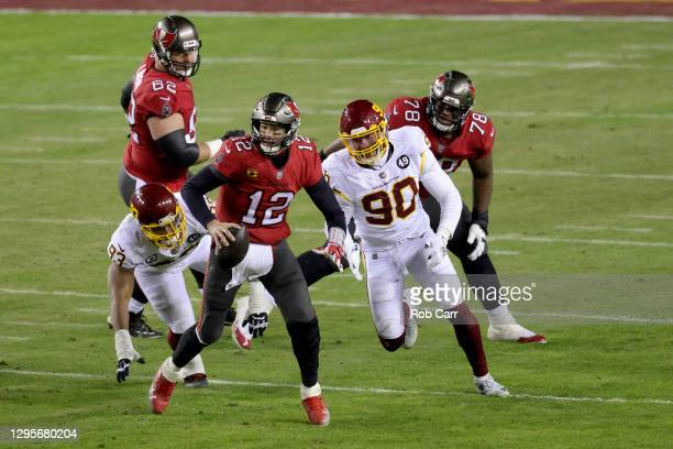 Quarterback Tom Brady of the Tampa Bay Buccaneers scrambles against the Washington Football Team during the second half of the NFC Wild Card playoff...
