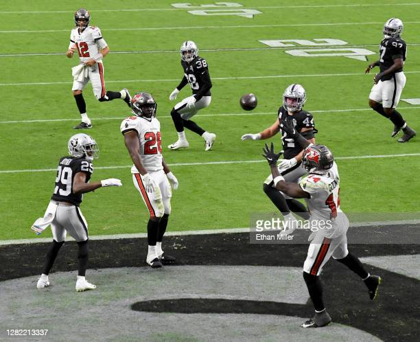 Quarterback Tom Brady throws a 4-yard touchdown pass to wide receiver Chris Godwin against the Las Vegas Raiders during the second half of their game...