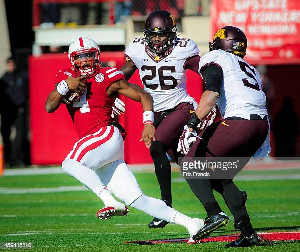 Quarterback Tommy Armstrong Jr #4 of the Nebraska Cornhuskers tries to elude linebacker Damien Wilson and linebacker De'Vondre Campbell of the...