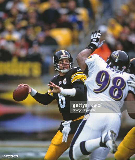 Quarterback Tommy Maddox of the Pittsburgh Steelers passes as he is pressured by defensive lineman Anthony Weaver of the Baltimore Ravens during a...